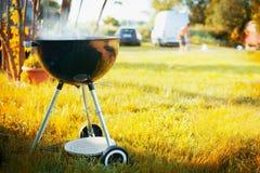 烤与烟在晚夏或秋天自然背景在一个公园或庭院有汽车和人剪影的  免版税库存照片