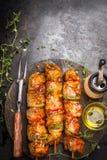 烤与用卤汁泡的串、肉叉子、草本香料和油的时间在黑暗的铁锈金属背景 图库摄影