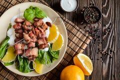 烤串做用猪肉和烟肉在与酸性稀奶油、调味汁和桔子的莴苣 免版税库存图片