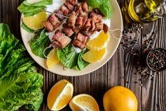 烤串做用猪肉和烟肉在与酸性稀奶油、调味汁和桔子的莴苣 库存照片