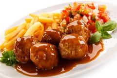 烤丸子、芯片和菜 免版税库存图片