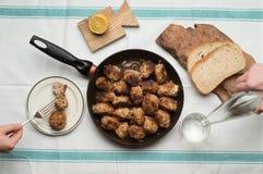 烤丸子的多汁重水多的部分服务用在一次老葡萄酒桌地道晚餐会的面包小圆面包 免版税图库摄影