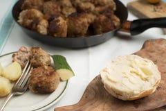 烤丸子的多汁重水多的部分服务用在一次老葡萄酒桌地道晚餐会的面包小圆面包 图库摄影