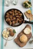 烤丸子的多汁重水多的部分服务用在一次老葡萄酒桌地道晚餐会的面包小圆面包 免版税库存图片