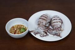 烤乌贼用泰国在白色板材的海鲜调味汁  免版税库存照片