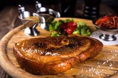 烤切片有骨头的猪肉腿 两个调味汁、红豆、葱、甜椒在木背景和黑玻璃  免版税库存图片