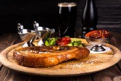 烤切片有骨头的猪肉腿 两个调味汁、红豆、葱、甜椒在木背景和黑玻璃  免版税库存照片