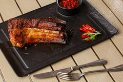 烤和烤肉热的排骨用辣椒和辣酱在黑石背景 ?? 断送为 免版税库存照片