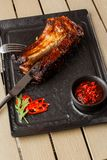 烤和烤肉热的排骨用辣椒和辣酱在黑石背景 ?? 断送为 免版税图库摄影