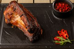 烤和烤肉热的排骨用辣椒和辣酱在黑石背景 ?? 断送为 免版税库存图片