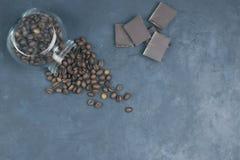 烤咖啡豆从一个玻璃瓶子倾吐了 一个咖啡对象的有角安置与巧克力片的 在黑暗的混凝土 视图 库存图片