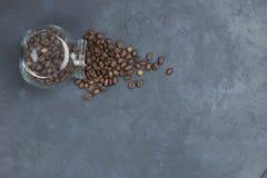 烤咖啡豆从一个玻璃瓶子倾吐了 咖啡对象的有角安置 在黑暗的混凝土 在视图之上 复制 库存图片