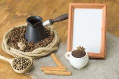 烤咖啡豆和八角在大麻圆环,在一cezve的心脏在一把木匙子旁边用多香果和白色fram 免版税库存图片