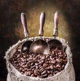 烤咖啡豆和铜瓢在老大袋 黑暗的bac 库存图片