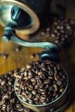 烤咖啡豆在一张木桌上自由地溢出了 在一个盘的咖啡豆碾碎的咖啡的 免版税库存图片