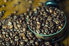 烤咖啡豆在一张木桌上自由地溢出了 在一个盘的咖啡豆碾碎的咖啡的 库存照片