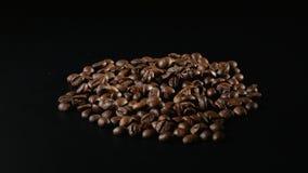 烤咖啡豆在黑背景转动 图库摄影
