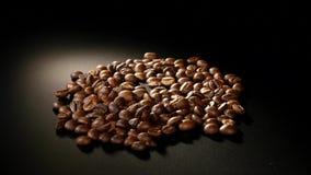 烤咖啡豆在黑背景转动 免版税库存照片