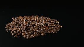 烤咖啡豆在黑背景转动 免版税图库摄影