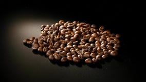 烤咖啡豆在黑背景转动 库存图片