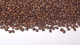 烤咖啡豆堆在白色的 库存照片