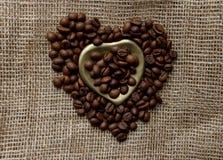 烤咖啡豆平的位置在一张桌布的与一个金黄心形的茶碟和咖啡杯 前杯早晨浓咖啡和 免版税图库摄影