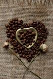 烤咖啡豆平的位置在一张桌布的与一个金黄心形的茶碟和咖啡杯 前杯早晨浓咖啡和 免版税库存照片