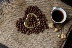 烤咖啡豆平的位置在一张桌布的与一个金黄心形的茶碟和咖啡杯 前杯早晨浓咖啡和 库存照片