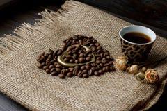 烤咖啡豆平的位置在一张桌布的与一个金黄心形的茶碟和咖啡杯 前杯早晨浓咖啡和 免版税库存图片