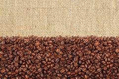 烤咖啡豆特写镜头在亚麻制纹理的 免版税库存图片