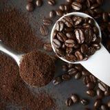 烤咖啡豆瓢和碾碎的咖啡匙子  免版税库存图片