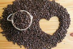 烤咖啡豆顶视图与心脏形状空间的在木桌上 免版税库存照片