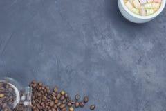烤咖啡豆,倒从有一杯白色咖啡的一个玻璃瓶子和蛋白软糖 有角安置  免版税库存照片