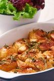 烤土豆用大蒜、麝香草和迷迭香在陶瓷烘烤盘,特写镜头 免版税图库摄影