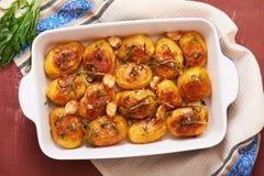 烤土豆用大蒜、麝香草和迷迭香在陶瓷烘烤盘,顶视图 免版税库存照片
