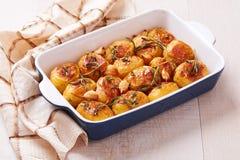 烤土豆用大蒜、麝香草和迷迭香在陶瓷烘烤盘 免版税图库摄影