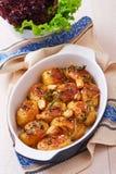 烤土豆用大蒜、麝香草和迷迭香在陶瓷烘烤盘 免版税库存图片