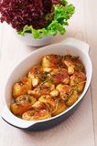 烤土豆用大蒜、麝香草和迷迭香在陶瓷烘烤盘 库存照片