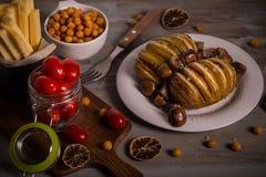 烤土豆用荷兰扁圆形干酪和蒜味咸腊肠在木板 免版税库存照片