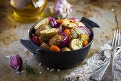 烤土豆用葱、红萝卜和大蒜 库存图片