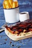 烤在一张蓝色木桌上的肋骨用油炸物 免版税库存图片