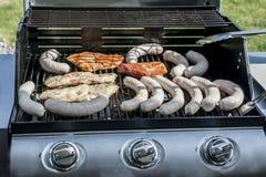 烤在丙烷气体格栅牛排多味腊肠香肠肉馅膳食的格栅bbq 图库摄影