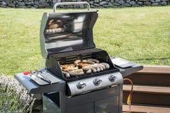 烤在丙烷气体格栅牛排多味腊肠香肠肉馅膳食的格栅bbq 免版税库存图片