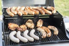 烤在丙烷气体格栅牛排多味腊肠香肠肉馅膳食的格栅bbq 免版税图库摄影