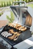 烤在丙烷气体格栅牛排多味腊肠香肠肉馅膳食的格栅bbq 库存图片