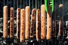 烤在便携式的烤肉的辣香肠在夏天去野餐 户外 烟,火 顶视图 免版税图库摄影