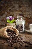 烤在大袋的咖啡在早晨光的木桌上 库存图片