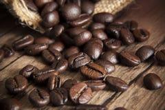 烤在木桌,宏观图象上的咖啡种子 免版税库存图片