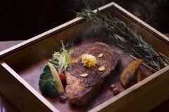 烤在木箱的熏制的安格斯眼睛牛排在黑背景中 免版税库存照片