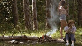 烤在火的两个女孩女朋友甜蛋白软糖在森林小组的晚上朋友野营 股票视频